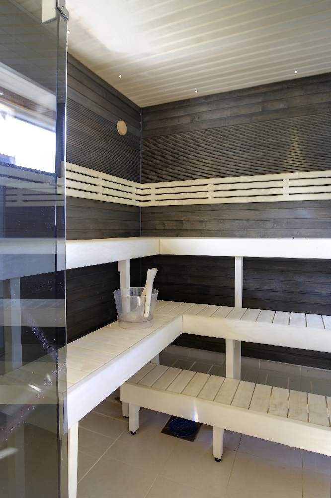 Omanäoline mustaks peitsitud saunasein.