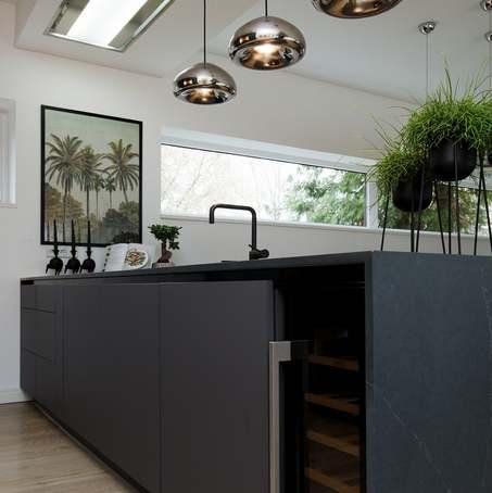 Kaasaegselt moodne - tumedast kõrgsurvelaminaadist köögimööbel. Õhupuhasti on lakke integreeritud.