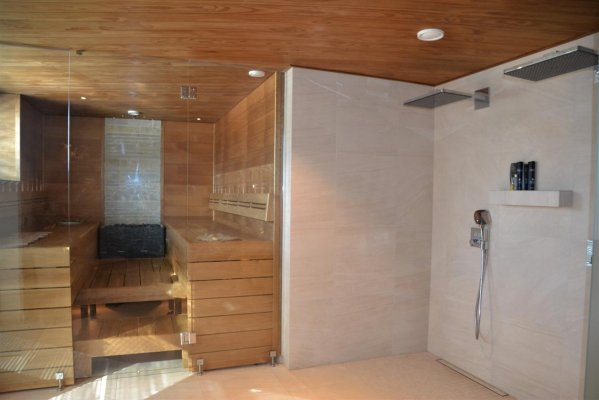 Pilt 15 - Sauna- ja leiliruumi muudab avarmaks täisklaasist seinaga paralleelselt lakke paigaldatud termopuit laudis, mis on mõlemas ruumis samal tasandil.
