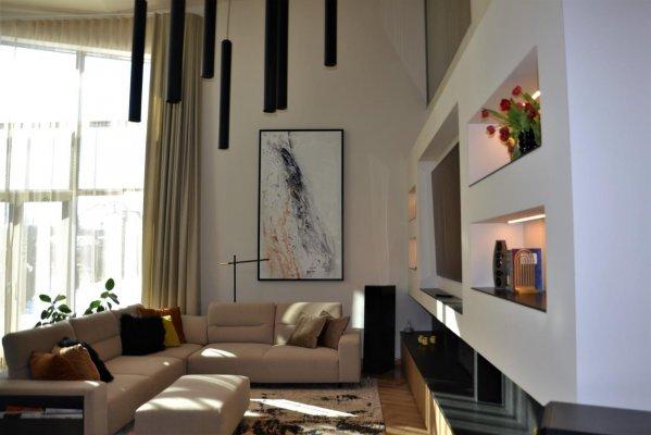 Pilt 5 - Huvitav lahendus on elutoas TV all. Seal on kamin, millest üks pool on näha elutoast ja teine saunast. Kaminat ümbritseb must graniit, mis jätkub seinal.