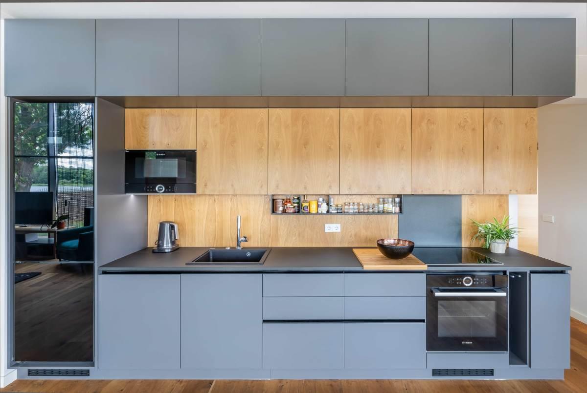 Köök-söögituppa projekteeriti funktsionaalne kõrge köögimööbel. Pererahva soovi kohaselt on külmkapi uks mustast klaasist, mis mõjub halli mööbli kõrval äärmiselt põnevalt.